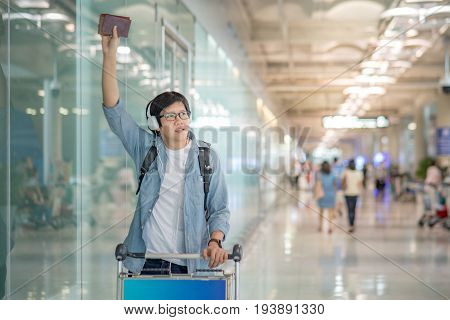 young asian man with airport trolley waving his hand in the international airport terminal arrival from travel abroad