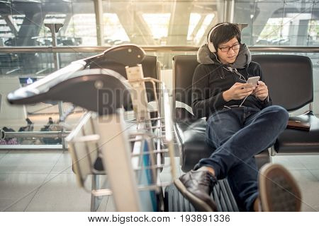 Young asian man using smartphone and listening to music while waiting for connecting flight on bench in the international airport terminal travel abroad concept