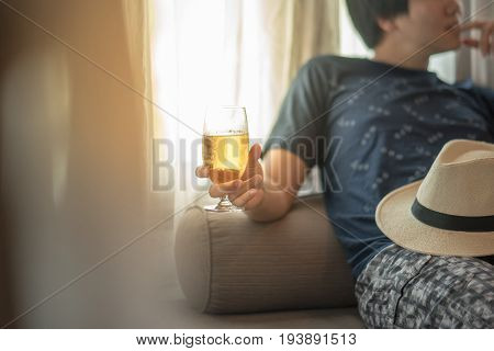 drunken man holding a glass of beer while lying on bed hangover after holiday party alcoholism or alcohol addiction concepts