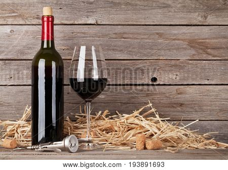 Red wine bottle and wine glass in front of wooden wall. With copy space