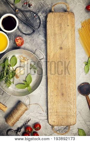 Olive oil, balsamic vinegar, salt, pepper, herbs, pasta, tomatoes on concrete background - cooking ingredients background-- top view - space for text. Healthy food, vegetarian or italian food concept.