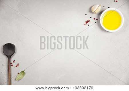 Olive oil, balsamic vinegar, pepper and herbs on concrete background - cooking ingredients -- top view - space for text. Healthy food vegan or diet nutrition concept.