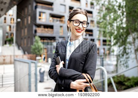 Portrait of a young woman realtor or businesswoman standing outdoors on the modern residential district background
