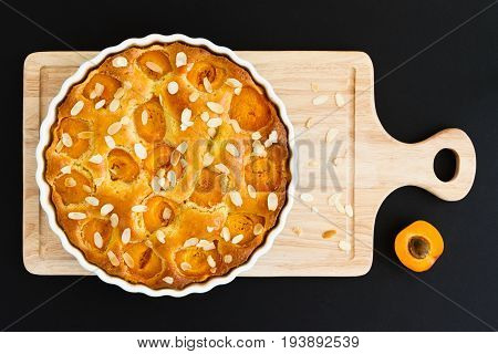 Apricot tart on a wooden chopping board, placed on a black backdrop