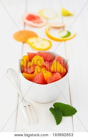 Fruit salad with oranges and grapefruits in a bowl, paring in the background
