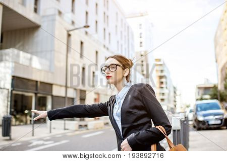 Young businesswoman catching a taxi standing on the street at the modern residential district