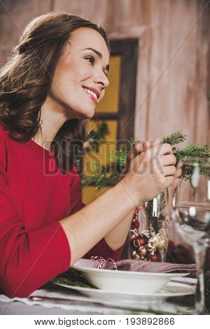 Attractive smiling woman sitting at holiday table decorated for Christmas