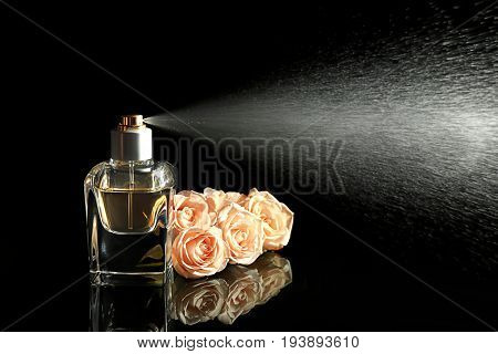 Spraying bottle of perfume and flowers on black background