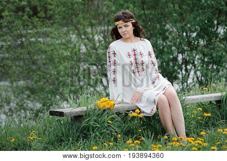 Portrait of a beautiful girl in Slavic clothes. Young woman with a bouquet of dandelions sitting on a wooden bench. Summertime