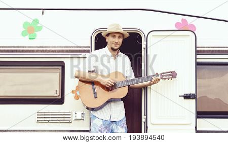 Handsome bearded hippy guy playing guitar outdoors at summer. Holiday, journey, vacation, trip concept.