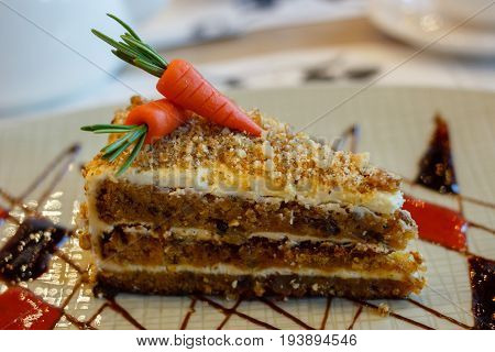 Sweet carrot cake decorated with marzipan and creme
