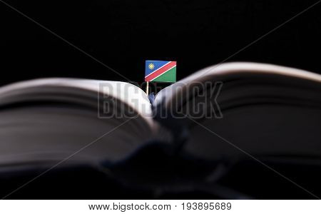 Namibian Flag In The Middle Of The Book. Knowledge And Education Concept.