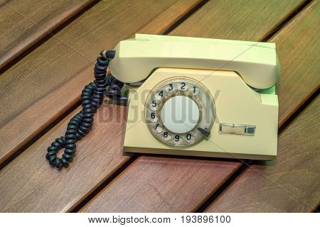 Close up vintage beige phone with disk on wooden background