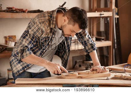 Carpenter working with chisel in shop