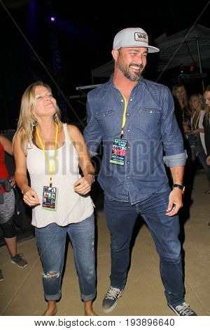 Taylor Kinney and an unidentified concert attendee on day 1 of the 2017 Temecula Valley Wine and Balloon Festival on June 2, 2017 at the Lake Skinner Recreation Area in Temecula, CA.