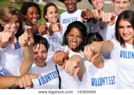portrait of a happy and diverse volunteer group pointing towards camera