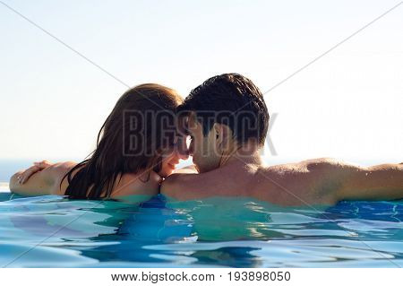 Young Couple Together in an Infinity Swimming Pool. Rear View of Honeymoon Couple at Luxury Resort. Travel and Summer Vacation Concept.