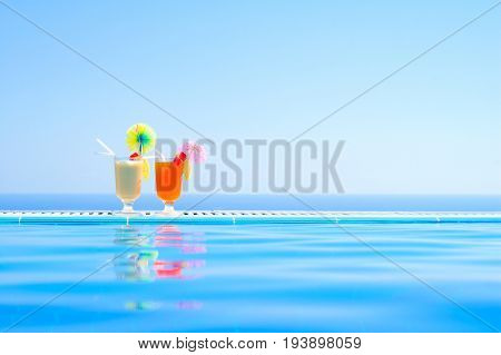 Two Colorful Tropical Cocktails near the Swimming Pool on the Background of Warm Blue Sea. Exotic Summer Vacation.