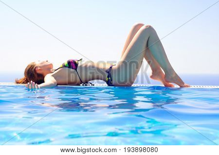 Young Beautiful Woman Relaxing by the Swimming Pool on the Background of Warm Blue Sea. Summer Vacation.