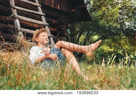Little lazy boy sleeps under old hayloft in garden