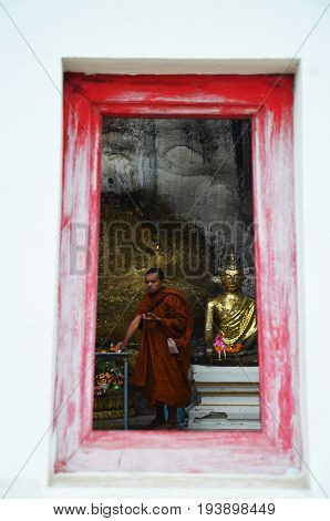 Monk Respect Praying And Gild Cover With Gold Leaf At Lord Buddha Image Appearing On A Cave Wall