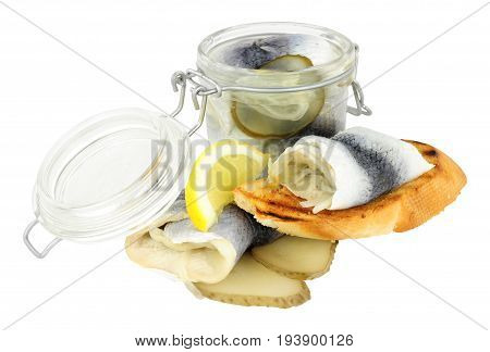 Pickled rollmop herrings in a glass storage jar and toasted bread isolated on a white background