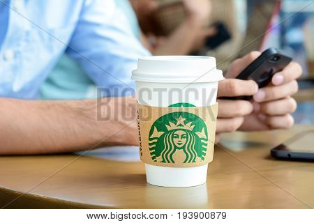 Bangkok Thailand - May 20 2015 : Starbucks paper coffee cup on the table with a man using smartphone as background in Starbucks coffee shop.