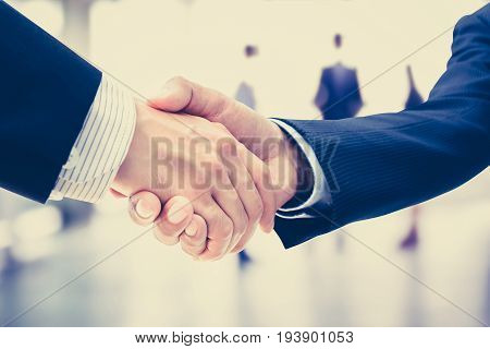 Handshake of businessmen on blur businesspeople background vintage tone - greeting dealing merger and a acquisition concepts
