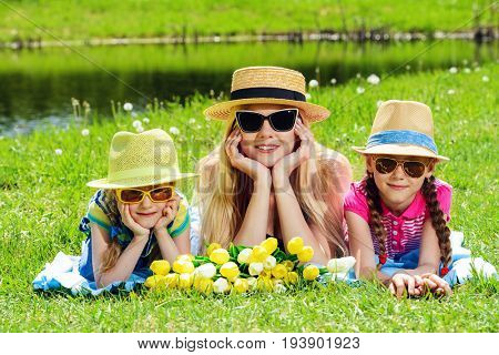 Cheerful girls with their beloved mother lying on a green lawn in the park. Summer holidays. Family concept.