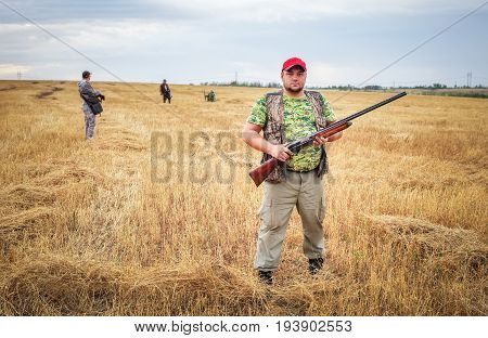 Group of hunters with a guns moving through the field looking for prey