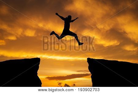 Man jumping over rocks with gap on sunset fiery background. Element of design.