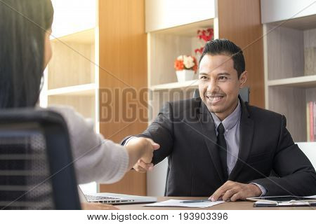 Asian businesspeople shaking hands greeting deal with each other at working place acceptation concept.