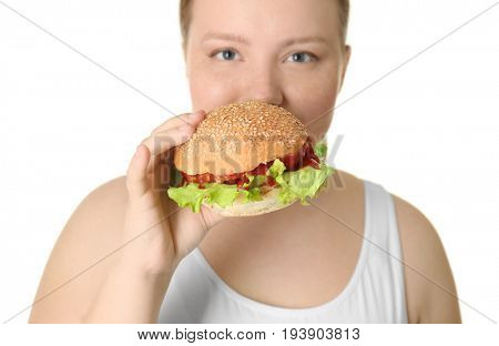 Overweight young woman with burger on white background. Diet concept