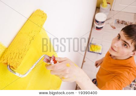 Young man painting the walls in a new house