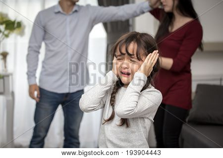 Little girl crying while parents quarrel. Closing the ears 5-10 years old family violence concept.
