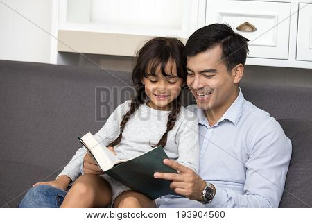 Happy Father Reading A Book With Daughter In Sofa, Happy Family Concept.