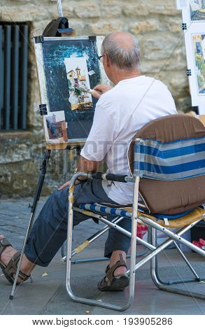 RONDA SPAIN - JUNE 2017: A Street artist at work painting the many beautiful buildings within Ronda Spain