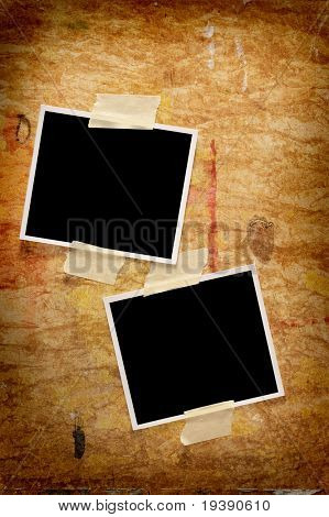 Two blank photographs on a grungy wooden background