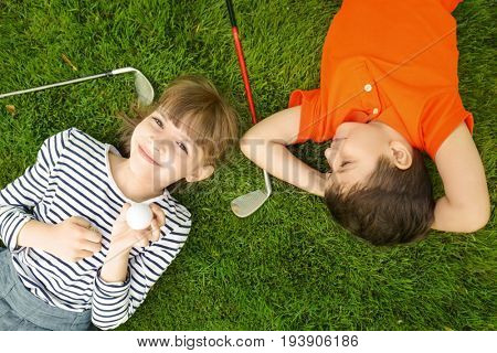 Cute children with ball and drivers lying on golf course