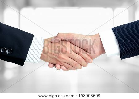 Handshake of businessmen on white room background - greeting dealing merger and a acquisition concepts