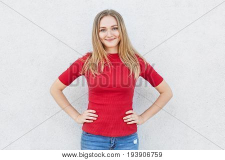 Glad Female With Light Hair And Blue Eyes Having Smile On Her Face Wearing Red Sweater And Jeans Hol