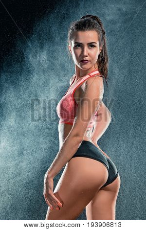 Young tanned fit woman with beautiful sporty buttocks and slim Waist with water drops at studio