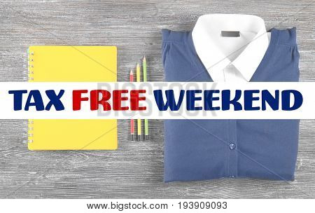 Text TAX FREE WEEKEND and school supplies with uniform on wooden background