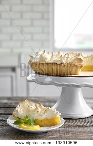 Composition with yummy lemon meringue pie on wooden table