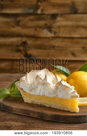 Piece of yummy lemon meringue pie on wooden table