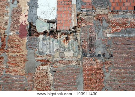 part of old derelict brick wall with several different bricks and cement patches after demolition work