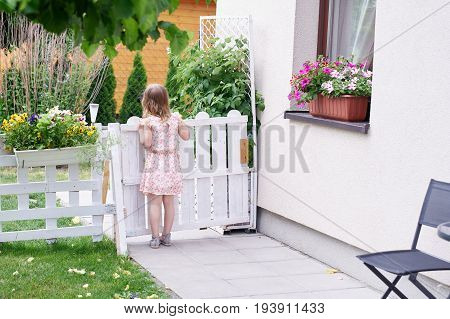 Little girl staying in a summer yard with her back to viewer and loooking with big interest outside the fence