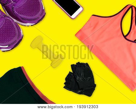 Sport clothes, trainers shoes, dumbbell, bra, top view. Fitness activity background, isolated equipment
