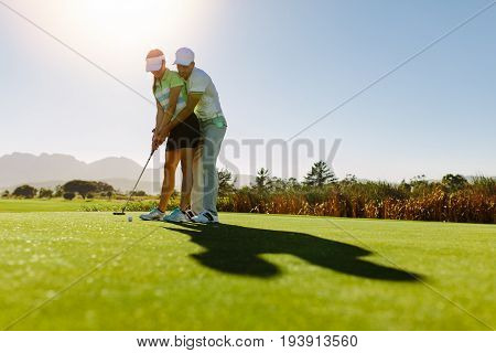 Male golf instructor teaching female golf player personal trainer giving lesson on golf course. Male showing woman to play golf.