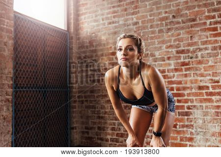 Young Woman In Sportswear Exercising Indoors.